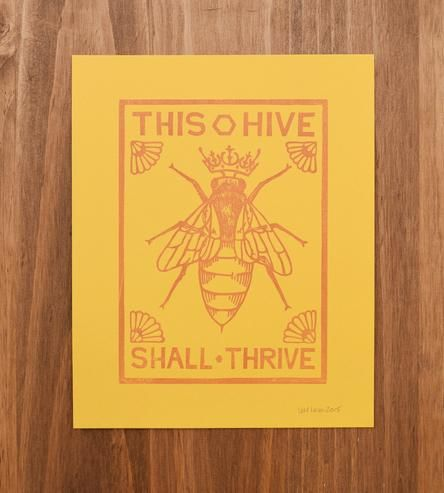 "Dress up your walls with this hand-carved queen bee art print. Reading, ""This hive shall thrive,"" in blocky type, each one has been letterpress printed from an original woodcut design. Hang it high to celebrate all of the bees in your hive."
