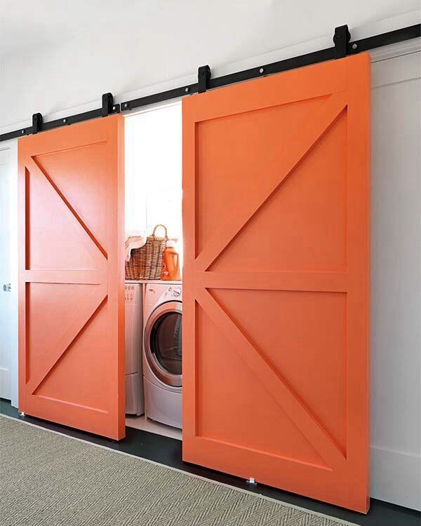 Washer and dryer play peek-a-boo behind orange barn doors.