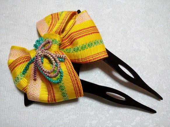 着物の帯の変わり結びを型どった撥型かんざし。正絹博多織を使用しており、博多織特有の人気の博多献上柄です。結び方は、アヤメ結びで、菖蒲の花弁が広がった華やかな印象となります。秋色の黄色を使用することで、秋の気配をイメージしています。秋祭りのお出掛け髪やお正月のお洒落髪や成人式、卒業式、七五三など色々な用途に合わせて戴けるのではと思います。着物を着るときに、帯の結び方を合わせて戴くと更にお洒落になると思います。