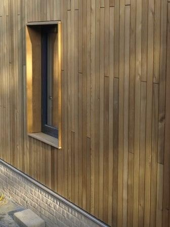 cedar cladding - vertical boards, deep 'framed' window reveals. The depth is good, but not sure of the framing of the window.