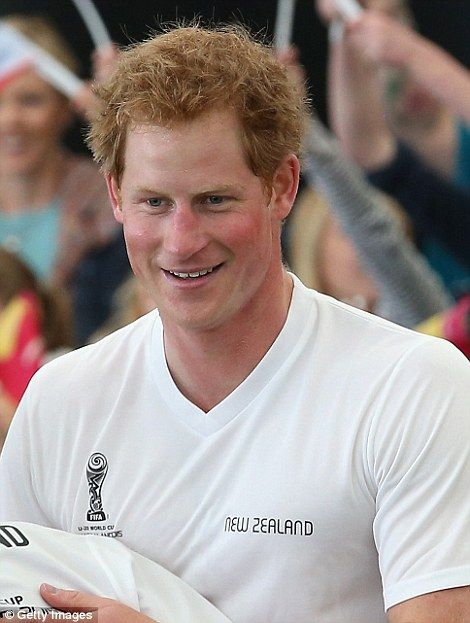 In high spirits: Prince Harry was smiling and flushed as he held his own against the young players