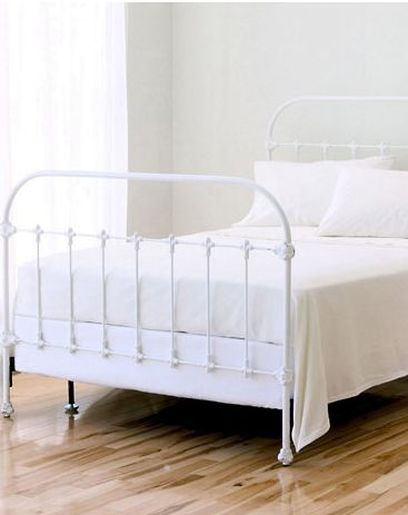 white cast iron bed on accent wall I between Windows.