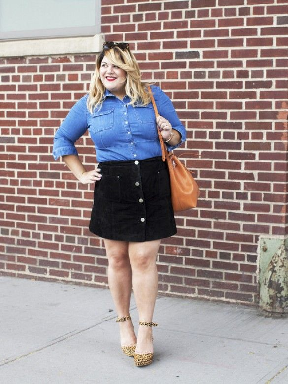 Nicolette Mason wears a denim button-down shirt, tortoiseshell sunglasses, black button-down skirt, animal print heels, and a tan leather bucket bag