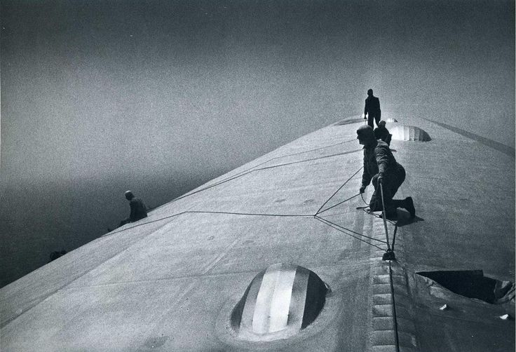 Image: Maintenance crewmen repairing the Graf Zeppelin in mid-air over the South Atlantic after it was damaged during a storm, 1934 #History