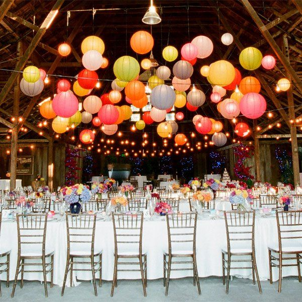 Colorful globe lanterns suspended over banquet tables contrast nicely against the rustic barn wood