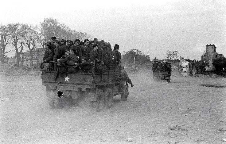 Deux camions GMC remplis de prisonniers allemands traversent un village en ruines, localisation inconnue.