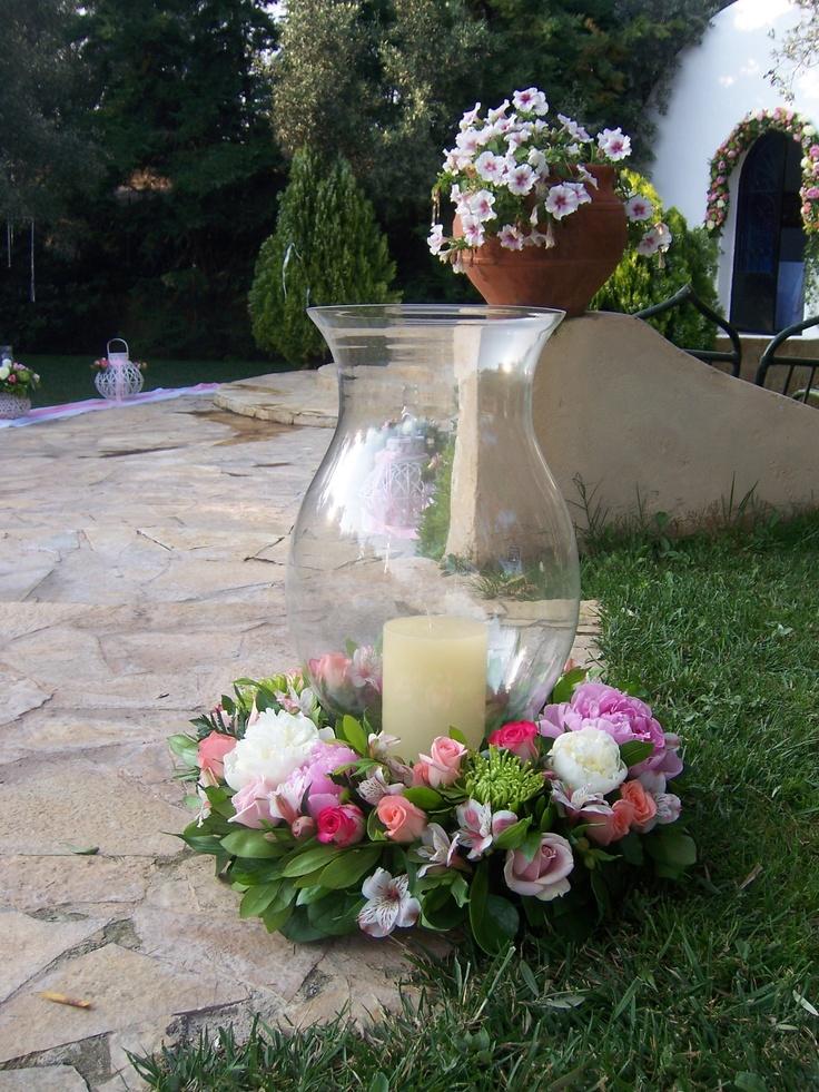 Στολισμός γάμου με μεγάλα κηροπήγια με λουλούδια και στεφάνι στη βάση στο κτήμα Νεφέλες. Τα λουλούδια στο στεφάνι έχουν παιώνιες λευκό και ροζ και τριαντάφυλλα σε ροζ χρώματα.