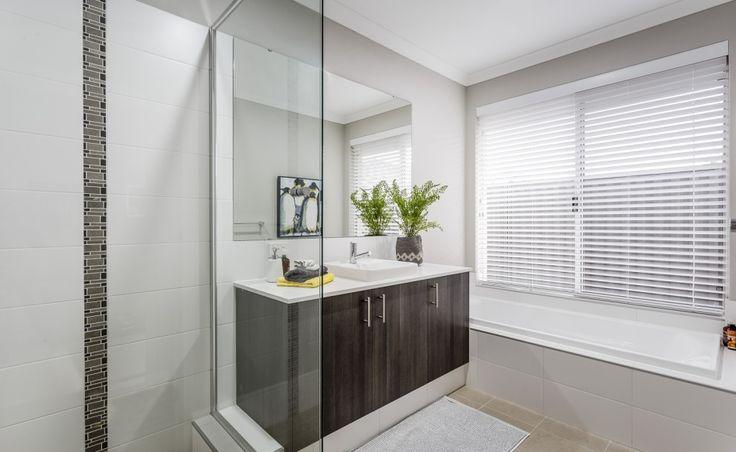 Bathrooms feature semi-inset vanity basins, mixer taps and glass semi-frameless…