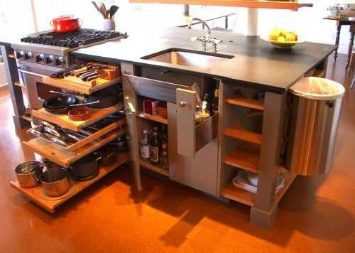 Super organized island. The top drawer is a knife rack and the third drawer has a pot-lid rack with adjustable steel rods. The space between the sink and the cabinet walls is just big enough for a drawer for tall bottles of olive oil and other cooking essentials. The apron front of the sink is actually a tilt-out tray to keep items handy, and there's a custom swing-out trash can for easy cleanup.