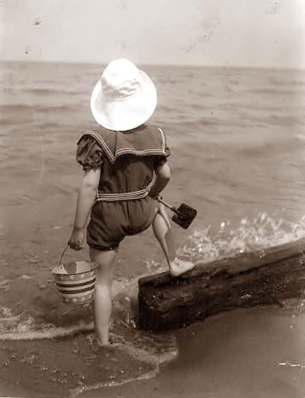 At the seashore, a little girl with her sand pail.