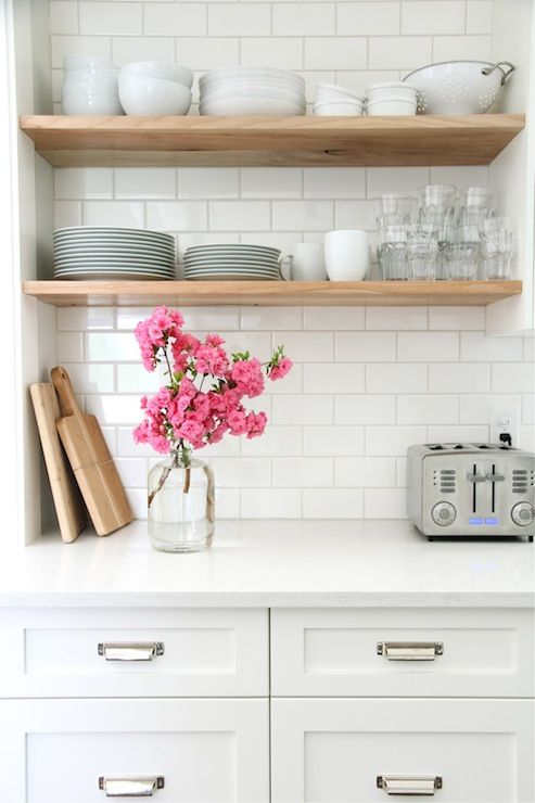 source: Our House Fabulous kitchen with white shaker cabinets painted Benjamin Moore Cloud White accented with Restoration Hardware Duluth Pulls paired with white quartz countertops and Home Depot subway tile backsplash. Kitchen features stacked floating shelves filled with glassware and pottery.