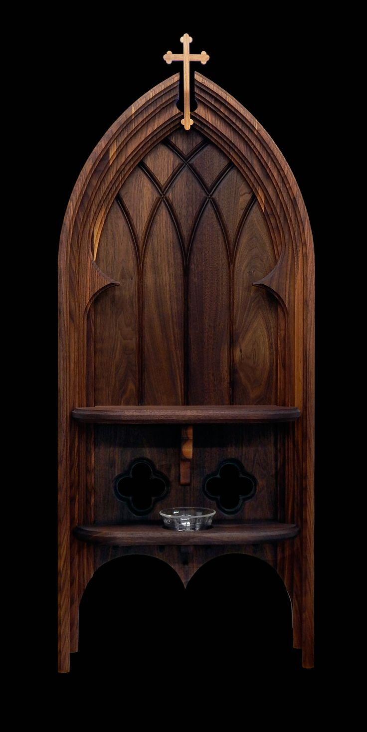 "Catholic home altar in black walnut with black cherry Budded Cross, quatrefoils, Holy Water font, and rosary hangers. Religious symbols and ornamentation were particularly important in the early Church when much of the laity were illiterate. ""Budded Cross"" - The four arms with three buds give the name Apostle's Cross, with one bud for each apostle, while Matthew 16:24 invites us all to become apostles, or disciples, of Christ."