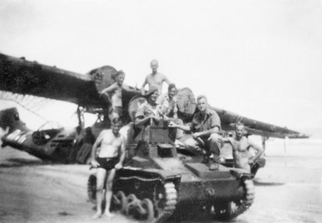 Australian soldiers posing with a captured Japanese Type 92 tankette and wrecked No. 42 Squadron RAAF Catalina aircraft, Balikpapan, Borneo, 1945