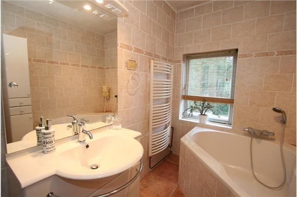 De badkamer is voorzien van hoekligbad, wastafelmeubel, wandcloset en designradiator.