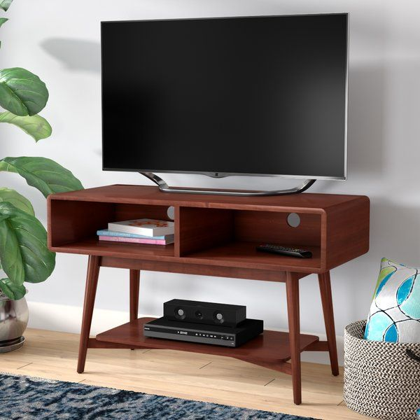Looking to liven up your living room? Add a splash of midcentury inspiration to your entertainment ensemble with this versatile TV stand, showcasing a simplistic silhouette with splayed legs and bringing modern appeal to your home. Crafted from manufactured wood with solid fir veneers, this mahogany-finished piece features cable management cutouts to prevent the tangled wires from cluttering your space. Top it with your flat-screen and tuck it into the corner of the room to make the most of…
