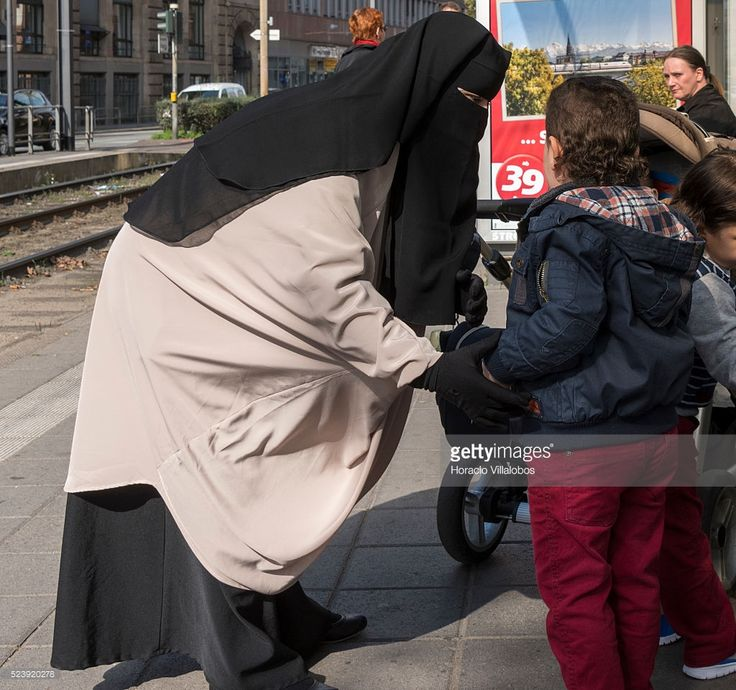 A woman wears niqab at Baselerplatz tram stop in Frankfurt, Germany, 26 September 2014. Although Germany has so far steered out of the issue, Hesse, a state run by CDU ruling party, has banned since 2011 Muslim face veils for its workers, because 'public sector workers must have neutral religious and political views'. A court in Bavaria has banned, on 22 April 2014, a 18-year-old Muslim student from wearing a face veil in class, rejecting her argument that she had a constitutional right to…