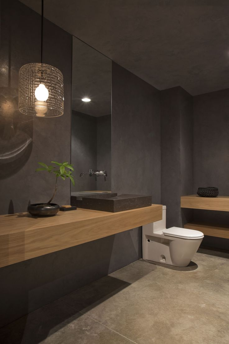 Grey bathroom with mid toned wood, wall hung wooden vanity, shelf/console, modern sanitary ware & toilet