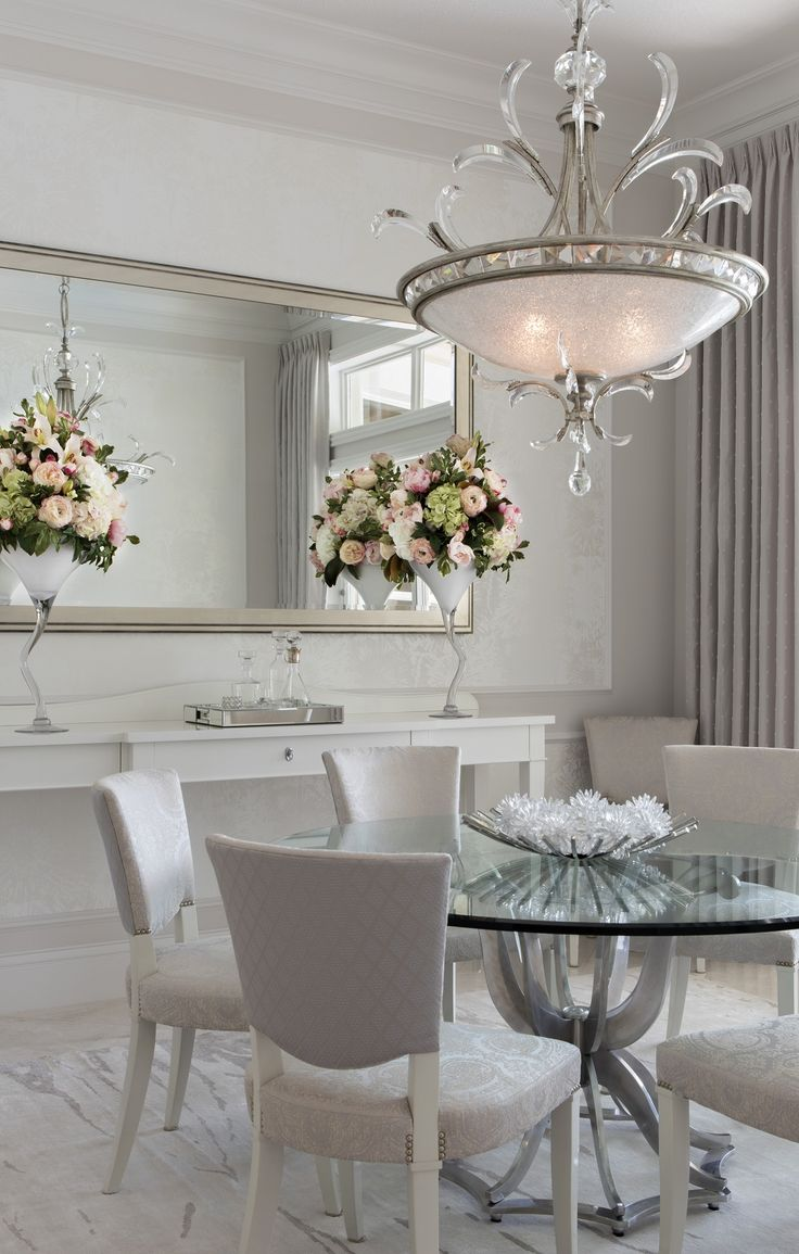 This dining room showcases an elegant chandelier with glamorous crystal detailing, which hangs above a dining table with a chrome base and a round glass top. The dining chairs flaunt different fabrics on the back and seat, both in a silvery gray but with slightly contrasting patterns. Two pastel floral arrangements in jagged glass vases stand on a white wooden sideboard with crystal pulls. The light gray area rug was custom-made. Interior design by Ingrid de Villiers, Robb & Stucky