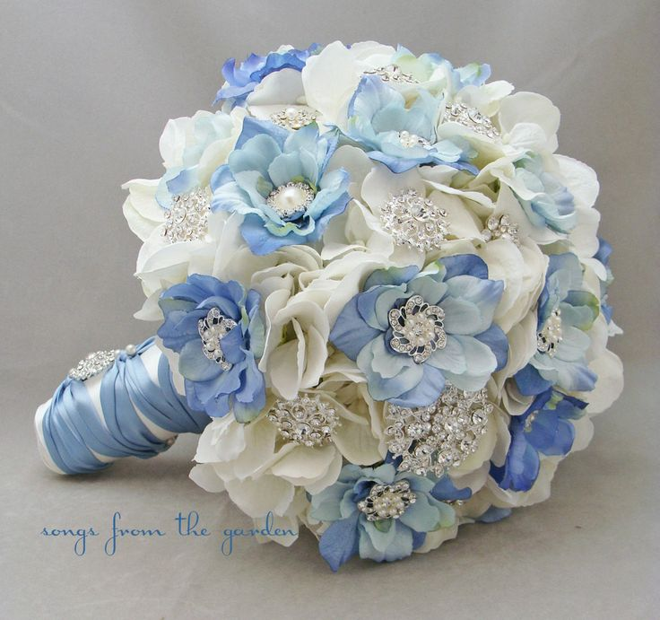 Silver rhinestone and pearl brooches and buttons and light blue and white silk blooms are a gorgeous pairing in this lush and lovely silk flower bridal bouquet with matching groom's boutonniere. This