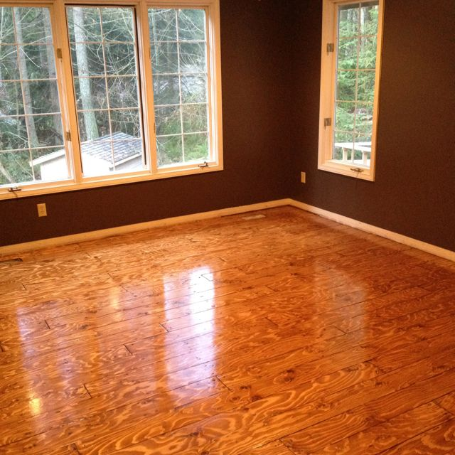 This was done using plywood. Cut it into planks and laid it like hardwood. WAY cheaper, and looks pretty decent!