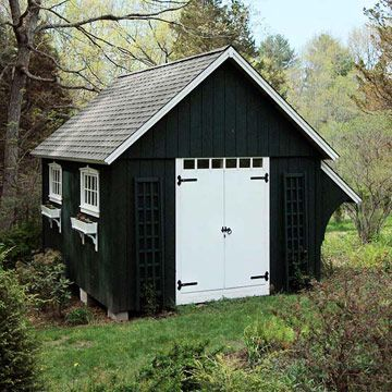 Inspired by the architecture of a traditional New England barn, this shed features board-and-batten construction. The double door allows storage of large equipment, such as riding lawn mowers and snow blowers. Decorative trellises flank the entry door, and window boxes beneath each of four symmetrically placed windows dress up the structure.