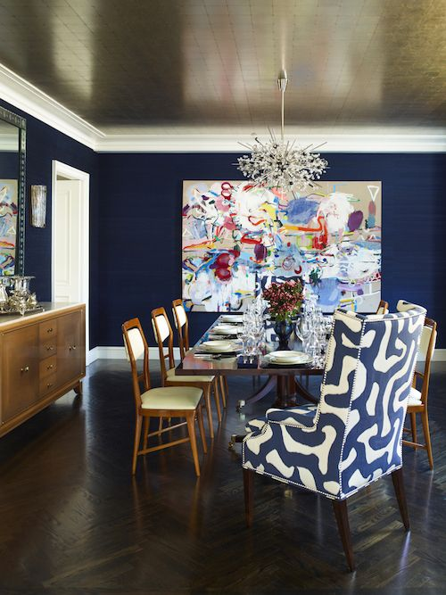 Metallic ceiling paper by Stark pops against the navy silk Designtex wallcovering in this Manhattan dining room by Mendelson Group. Vintage Carlo di Carli side chairs are from Van den Akker, and the host chair is upholstered in a John Rosselli fabric with nailhead trim.