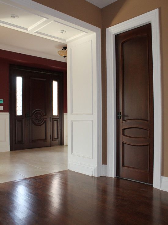 I love the contrast of the brown doors and white molding. beautiful.