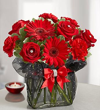 Red roses, red gerberas and frilly red carnations are gathered in a glass rectangle vase wrapped in lacey black organza. Finished with a red rhinestone band and rhinestone pins in the roses.