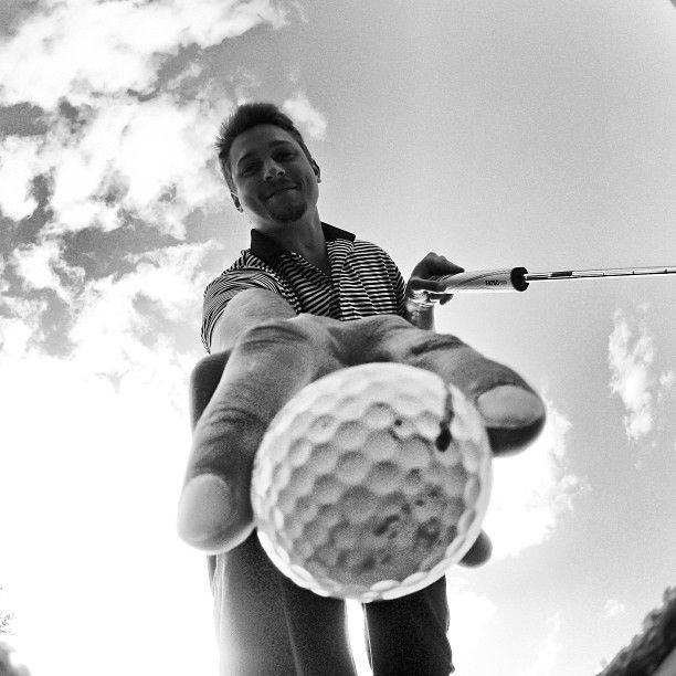 Golfer Matthew Japchen retrieves his golf ball.