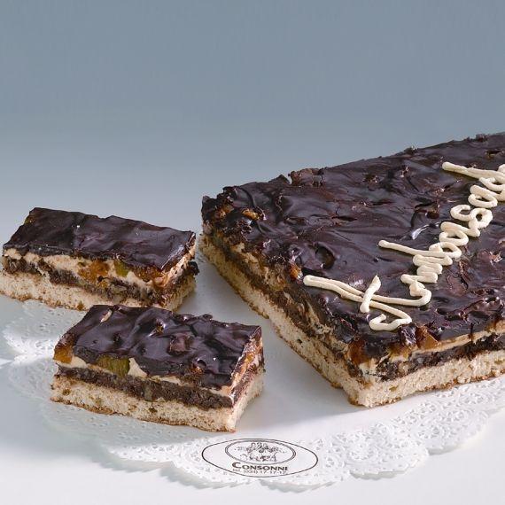 Ambasador Oryginalne ciasto kremowe z cienkim biszkoptem, przełożone masą czekoladową z migdałami, orzechami, rodzynkami oraz masą maślaną z brzoskwiniami, mandarynkami i kiwi. Jako ozdoba polewa czekoladowa.