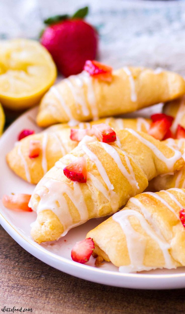 These easy strawberry lemon cheesecake croissants (aka strawberry lemon cheesecake crescent rolls) are made with just 6-ingredients! No bake strawberry lemon cheesecake filling is stuffed inside of crescent roll dough and baked until golden brown and topped with a homemade lemon glaze! Plus, a step-by-step video below!
