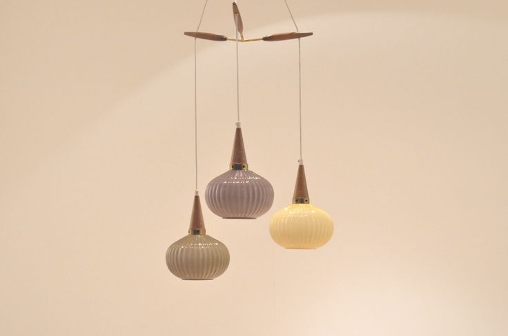 "Pendant lamp composed of three hanging opaline glass ""lanterns"" in a grey, purple and yellow. The lamps are suspended from a brass and teak wood suspension rig at alternating heights."