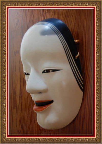 Это маска молодой женщины, используемая для спектаклей театра Но, показывает характерные знаки японской красоты. Маска театра олицетворяет красоту стандартов эпохи Хэйан в Япония - белое лицо, розовый бутон рта, черные зубы и высоко окрашенные брови.