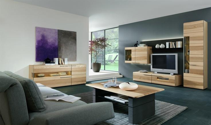 Ein Ort der Stille und Ausgeglichenheit: Diese Wohnzimmergestaltung lässt Sie entspannen und vom Alltagsstress abschalten. Kieselsteingrau in Verbindung mit hellen Holztönen lassen Gemütlichkeit entstehen, weiße Farbflächen veredeln den Raum. Das Grau wirkt bodenständig, wird aber durch die hellen Holzmöbel ein wenig aufgelockert. Stilvolle Grünpflanzen sorgen für ein gelungenes Wohnambiente. Das ausgedehnte Sofa lädt zum gemütlichen Relaxen ein, während kräftige Farbakzente das Flair…