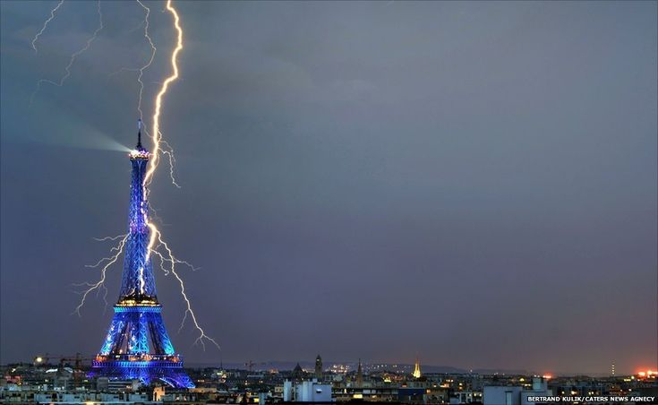 A lightning bolt appears to strike the iconic Eiffel Tower while the Paris landmark is seen illuminated in vibrant blue lights. Bertrand Kulik/Caters News Agency