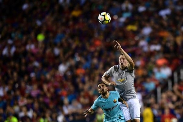Barcelona's forward Paco Alcacer (L) and Manchester United's defender Phil Jones jump for a ball during the second half of the FC Barcelona vs. Manchester United FC 2017 International Champions Cup match July 26, 2017 in Landover, Maryland. / AFP PHOTO / Brendan Smialowski