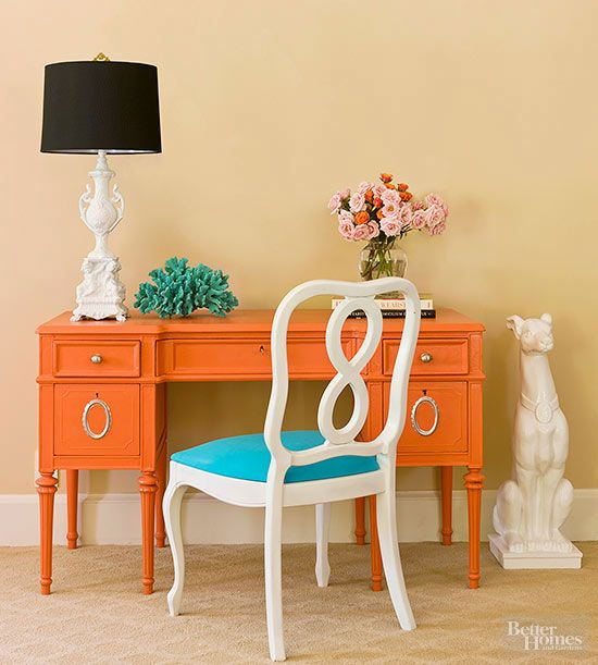 Bright orange paint minimizes intricate details and brings this desk into modern fashion while silver details add sparkle./