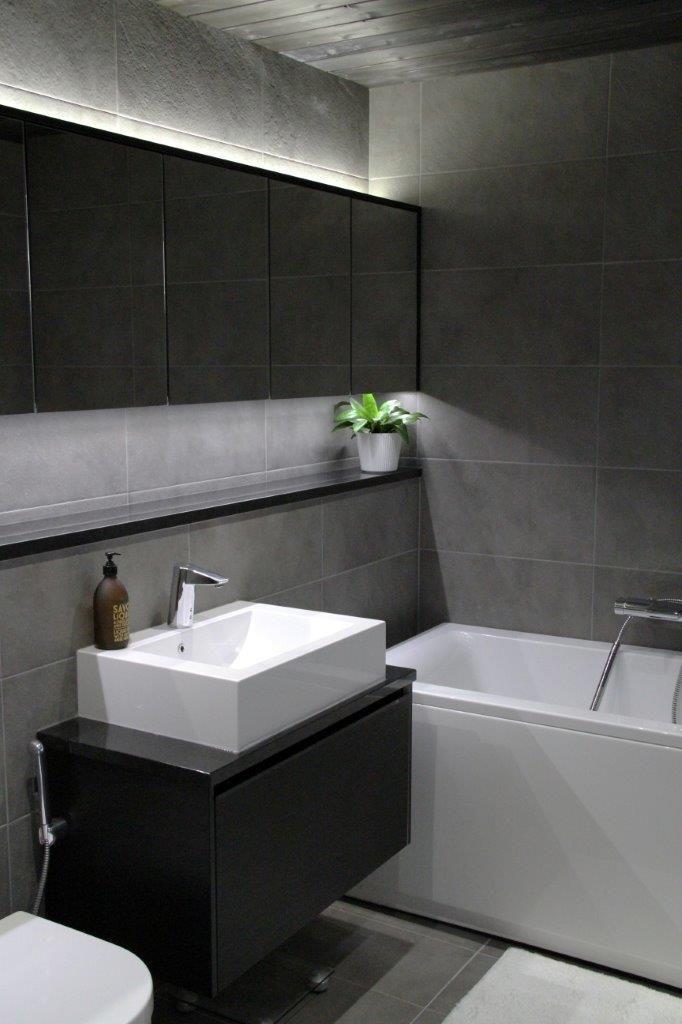 Levollista kylpylätunnelmaa luovat harmaat kivikuvioiset laatat, valopeili sekä kontrasti mustan allaskaapin ja valkoisen kylpyammeen välillä. #puuvaja