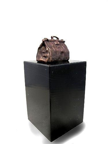 beeldje van een doktetstas. Breedte van de tas is 42 mm, staat op een sokkel van graniet 50x50x80 mm.