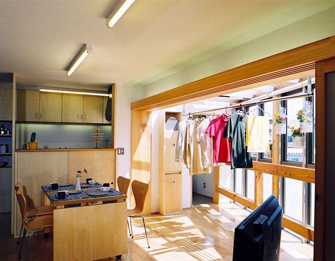らあめん店の忙しい毎日のことを考えて、どんな天気の日でも洗濯物が干せるサンルームをリビングの延長に作りました。サンルームとの境目には、中空ポリカーボネート製の引戸を設け、それを閉めることで、来客時の目隠しになったり、暑さ、寒さを遮ったりする役目をします。この写真「室内干しのできるリビングダイニング」はfeve cas...