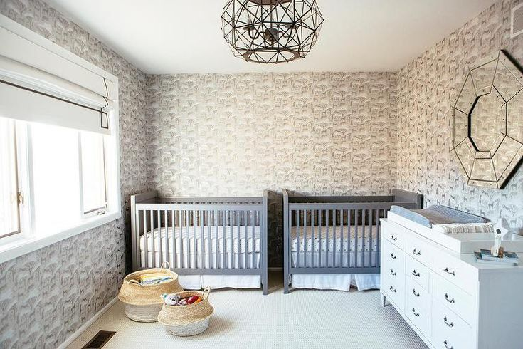 Gray twin boys nursery design includes side by side cribs with white sheets and matching white skirts surrounded by cheetah safari print wallpaper.