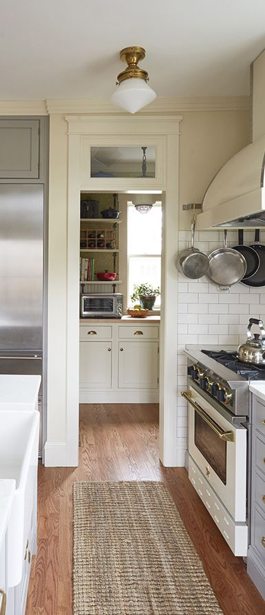 BlueStar Kitchen Design Contest Winner | Rebekah Zaveloff | A farmhouse sink with a brass deck mount faucet is fixed to a white quartz island top. Subway tile clads the walls and are complemented by creamy marble countertops and BlueStar range.
