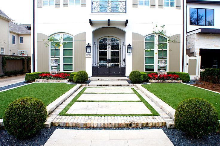 Front view of this French Contemporary Villa captures the symmetry of the front lawns and walking path. Sharply trimmed boxwood hedges frame color beds of Cyclamen which accent mirrored sculpted planters. White brick separates the articial lawn from borders of blackstar gravel.