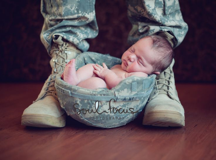 Newborn baby in army helmet