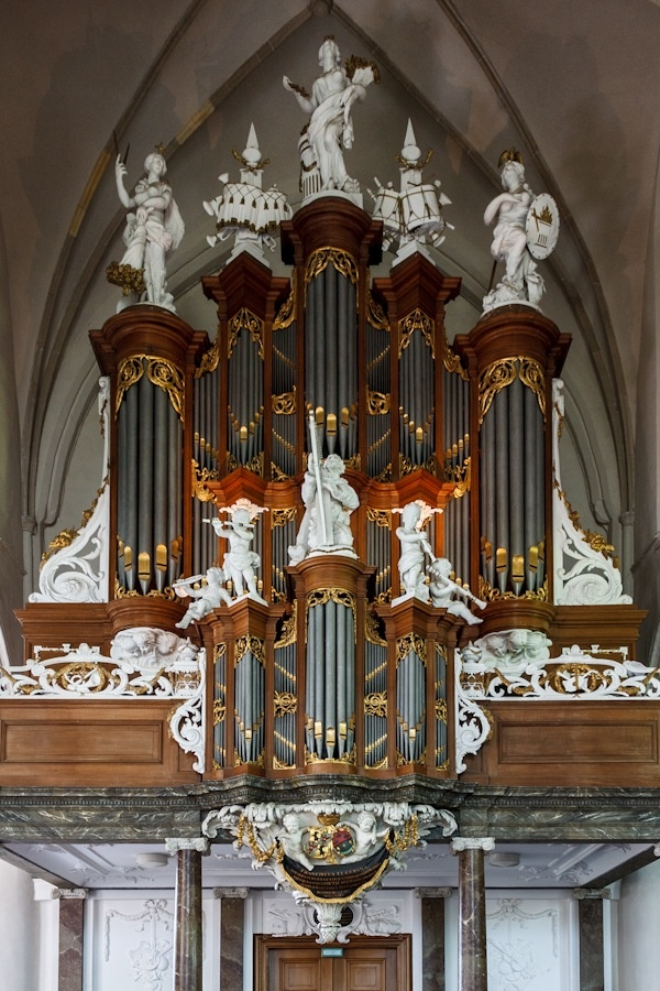Extravagantly decorated organ in Martini Church, Bolsward, Netherlands, built 1781.  Though large and stalwart, the exterior belies the magnificence of the organ pipes which are about the only decoration in the sanctuary.