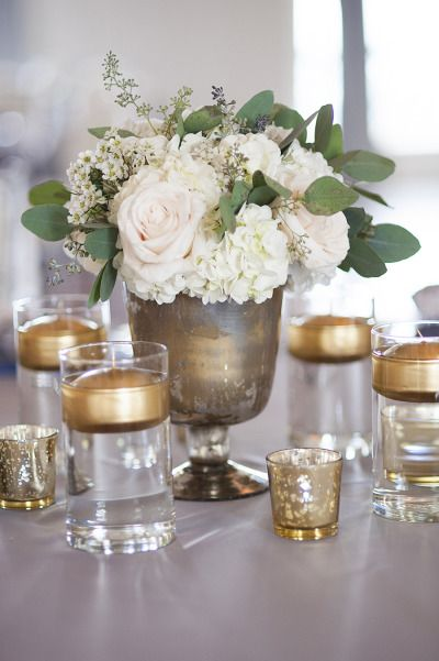 Pretty flowers and gold candles in vases: http://www.stylemepretty.com/2014/09/26/classic-wedding-by-christina-leigh-events/ | Photography: Ely Fair - http://elyfairphotos.com/