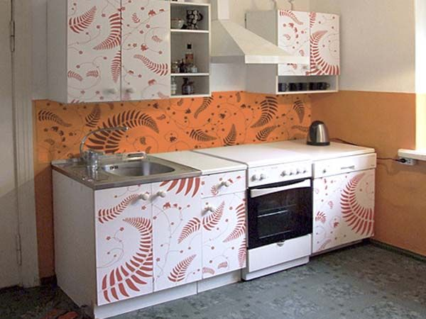 orange wall paint and kitchen cabinets decorated with vinyl stickers