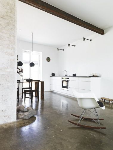 White eames rocker. Lovely pendants. Concrete floor.