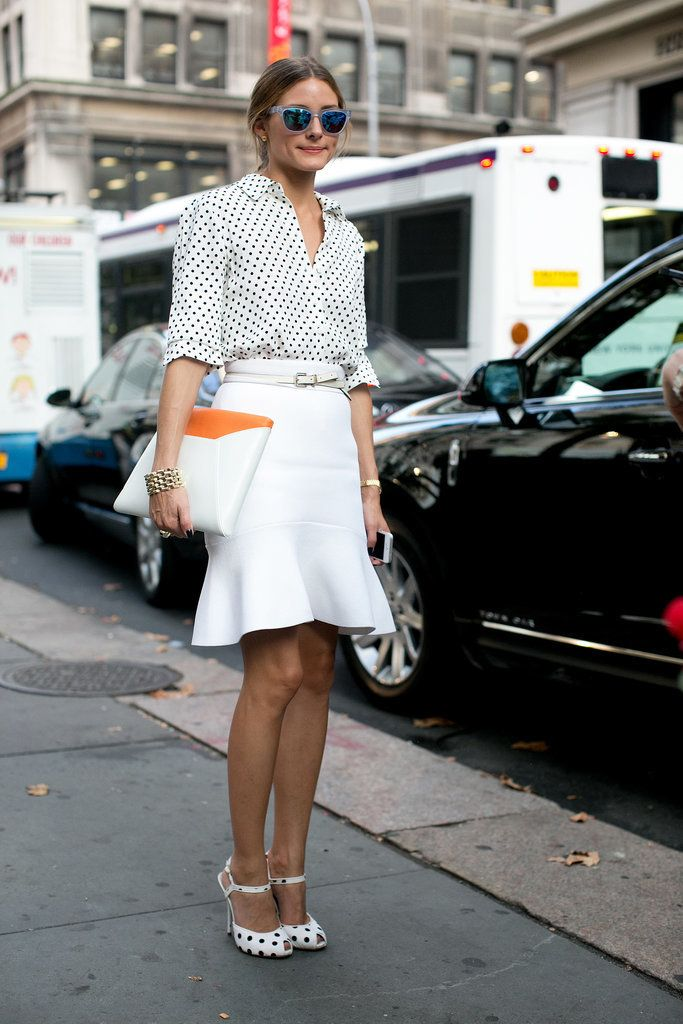 Olivia wearing a business outfit.polka dots shirt,white skirt,matching polka dots sandals and big white and orange clutch.i love the waste belt too!just so stylish