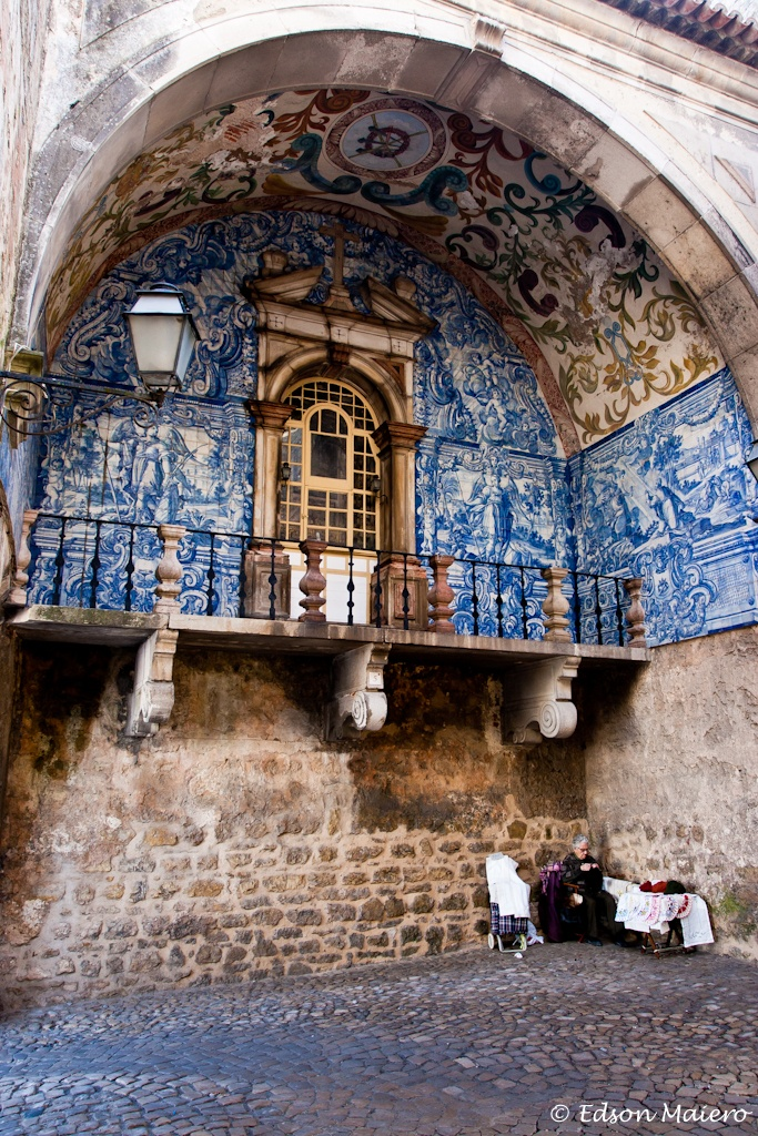 Óbidos: Uma senhora vende bordados na Porta da Vila, revestida com azulejos do século XVIII